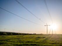 Энергосистема и электрические провода в заходе солнца стоковые фотографии rf