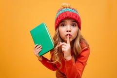 Энигматичная маленькая девочка в свитере и шляпе держа книгу Стоковое Изображение RF
