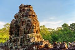 Энигматичные гигантские каменные стороны виска Bayon в солнце вечера Стоковое Изображение
