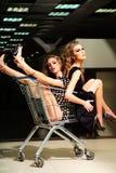Энигматичные девушки с вагонеткой покупок Стоковые Фото