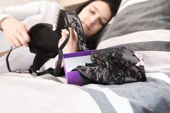 Эротичное нижнее белье в подарочной коробке лежа на кровати Стоковое Изображение