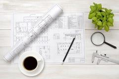 Эскизы, увеличитель, чашка кофе и комнатное растение чертежа на деревянной поверхности Стоковая Фотография RF