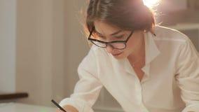 Эскизы чертежа модельера для одежд в atelier Счастливый молодой модельер работая в мастерской