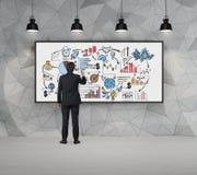 Эскиз чертежа бизнесмена на whiteboard в конкретной комнате Стоковые Изображения