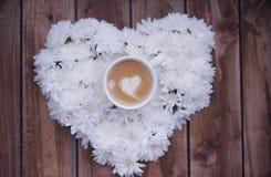 Эспрессо в цветах с сердцем на деревянной предпосылке стоковые изображения