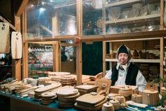 эстония tallinn Продавец старухи продает различные естественные деревянные ремесла на рождественской ярмарке зимы Стоковые Изображения RF