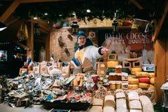 эстония tallinn Продавец человека в традиционной рождественской ярмарке продает сыр и другие молочные продукты на площади ратуши Стоковые Фото