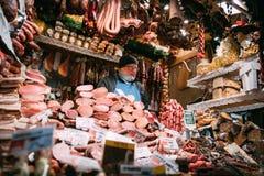 эстония tallinn Продавец человека в традиционной рождественской ярмарке продает сосиску и другие мясные продукты на площади ратуш Стоковая Фотография RF
