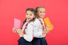 Эти книги совершенно гений Дети гения маленькие усмехаясь на красной предпосылке Счастливые девушки гения или дети интереса стоковые изображения