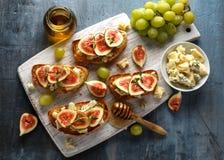 Эти tartines смоквы и горгонзоли, тост, bruschetta заморошенный с медом на белой деревянной доске стоковое изображение