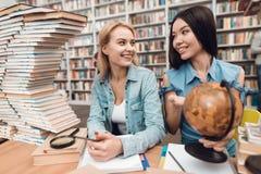 Этническая азиатская девушка и белая девушка окруженная книгами в библиотеке Студенты используют глобус Стоковое Фото