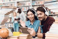 Этническая азиатская девушка и белый парень окруженные книгами в библиотеке Студенты используют таблетку с наушниками Стоковое фото RF