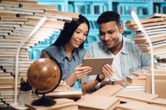 Этническая азиатская девушка и индийский парень смешанной гонки окруженные книгами в библиотеке Студенты используют таблетку Стоковая Фотография