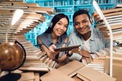 Этническая азиатская девушка и индийский парень смешанной гонки окруженные книгами в библиотеке Студенты используют таблетку Стоковое фото RF