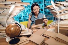 Этническая азиатская девушка окруженная книгами в библиотеке на ноче Студент слушает к музыке на таблетке стоковое фото rf