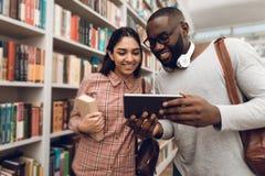 Этническая индийская девушка смешанной гонки и черный парень в библиотеке Студенты используют таблетку Стоковая Фотография