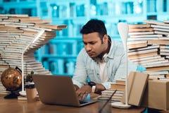 Этнический индийский парень смешанной гонки окруженный книгами в библиотеке Студент использует компьтер-книжку стоковые фото