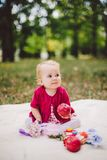 Этничность белокурое одно маленького ребёнка кавказская годовалое от рождения сидит на шотландке на зеленой траве в парке и держи стоковые фото