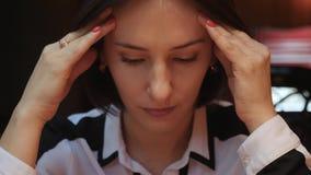 Это видео около близко вверх по взгляду молодой женщины закрывая ее глаза, касается ее лбу, имеющ головную боль, массажирует ее в видеоматериал