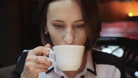 Это видео около молодая привлекательная бизнес-леди выпивает чай кофе в ресторане сток-видео