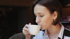 Это видео около молодая привлекательная бизнес-леди выпивает чай кофе в ресторане акции видеоматериалы