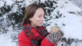 Это видео о конце-вверх стороны девушки которая выпивает горячие чай или кофе в зиме на улице, она носит связанный mit видеоматериал
