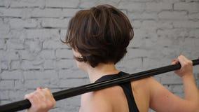 Это видео о красивой молодой атлетической sporty женщине делая назад низкую cardio разминку в спортзале Задний бортовой конец вве акции видеоматериалы