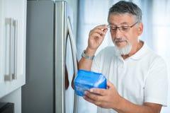 Это все еще точно? Старший человек в его кухне холодильником стоковое фото rf