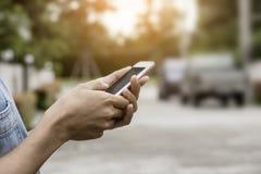 Это изображение изображение женщины используя мобильный телефон с домом и автомобилями на заднем плане Стоковое Фото
