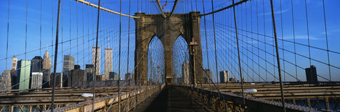 Это close-up дорожки Бруклинского моста к Манхаттан Горизонт Манхаттан на заднем плане Ограждать стали o стоковые фото