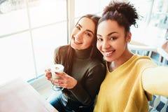 Это selfie 2 красивых девушек которые смотрят настолько изумительными и счастливыми в то же время Они в кафе выпивая некоторое стоковые фотографии rf