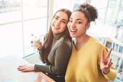 Это selfie 2 красивых девушек которые смотрят настолько изумительными и счастливыми в то же время Они в кафе выпивая некоторое стоковое изображение