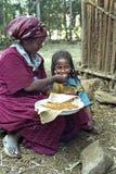 Эфиопская женщина дает injera дочери для еды Стоковая Фотография