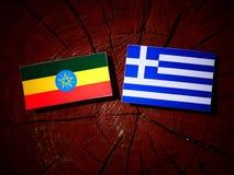Эфиопский флаг с греческим флагом на изолированном пне дерева Стоковое Фото