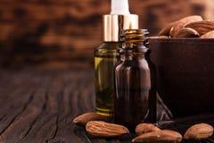 Эфирное масло миндалины на деревянной предпосылке Стоковая Фотография RF