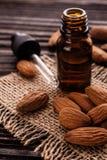 Эфирное масло миндалины на деревянной предпосылке Стоковое Изображение