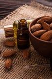 Эфирное масло миндалины на деревянной предпосылке Стоковое Изображение RF