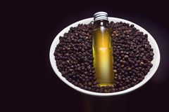 Эфирное масло черного перца на шаре черного перца стоковая фотография