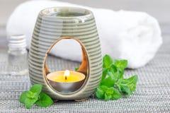Эфирное масло пипермента в лампе ароматности на серой циновке с предпосылкой курорта Стоковые Фото