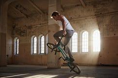 Эффектное выступление BMX и катание скачки в зале с солнечным светом Стоковые Фото