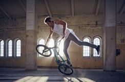 Эффектное выступление BMX и катание скачки в зале с солнечным светом Стоковая Фотография