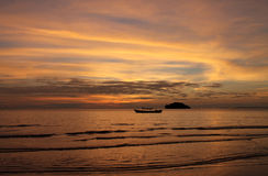Эффектный заход солнца над шлюпкой и морем длинного хвоста Стоковая Фотография