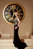 Элегантная дама в моды платье черноты длиной представляя перед настенными часами Стоковое Изображение