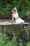 Элегантная женщина на береге пруда леса стоковое изображение
