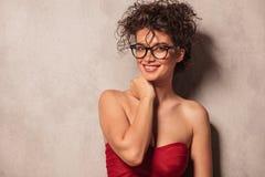Элегантная женщина нося сексуальное красное платье и стекла стоковая фотография