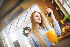 Элегантная женщина смотря smartphone пока сидящ на таблице около больших окон в ярком уютном кафе Стоковые Изображения