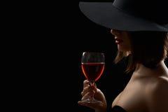 Элегантная загадочная женщина в шляпе держа стекло красного вина дальше Стоковое фото RF