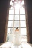 Элегантная красивая невеста свадьбы представляя около большого свода окна Стоковые Фото