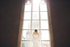 Элегантная красивая невеста свадьбы представляя около большого свода окна Стоковое Изображение RF