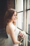 Элегантная красивая невеста свадьбы представляя около большого свода окна Стоковые Изображения RF